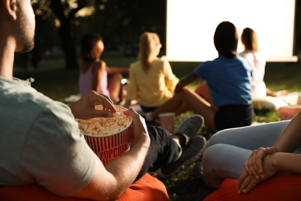 Group of young people sat watching open-air cinema with popcorn. Toghill House Farm. What to do in Bath.